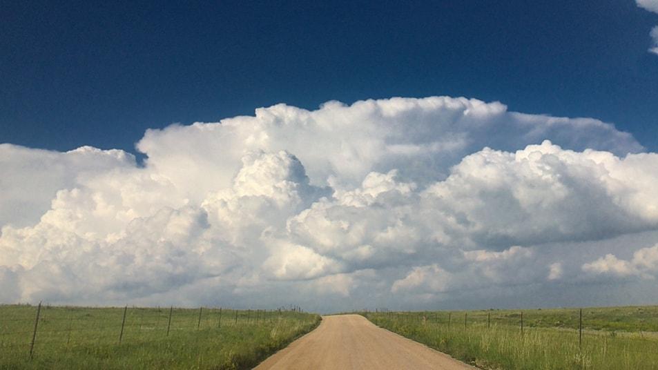 A photograph of a cumulonimbus capillatus incus cloud (Cb cap inc) above a road