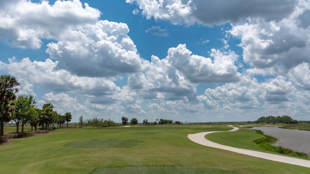 A photograph of cumulus mediocris clouds (Cu med) over a golf course in Florida