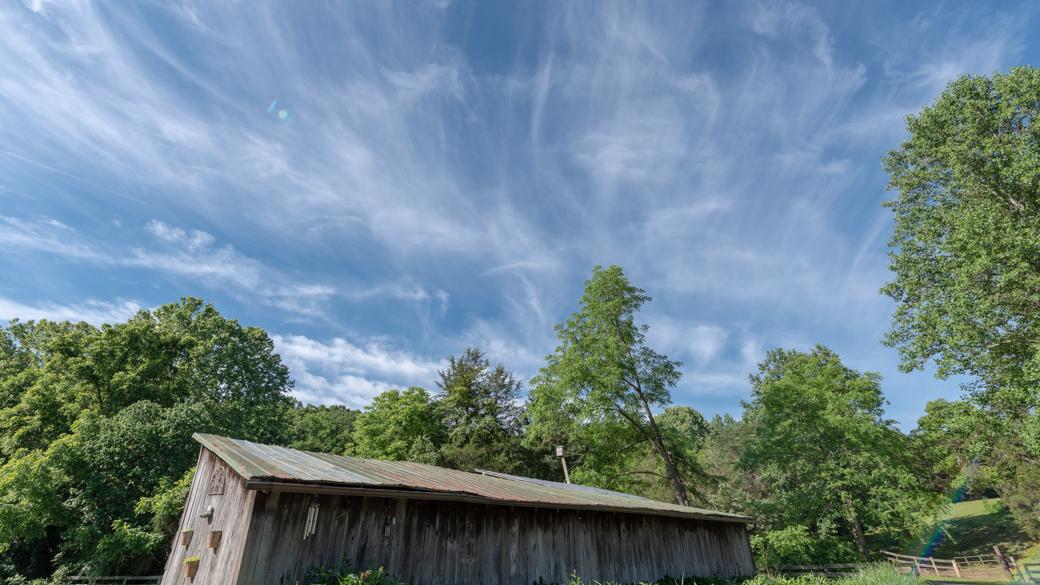 A photograph of cirrus fibratus duplicatus clouds (Ci fib du) over a barn