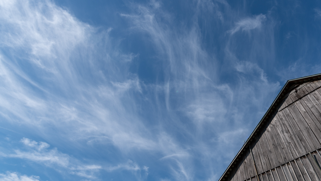 A photograph of cirrus fibratus intortus clouds (Ci fib in) over a barn