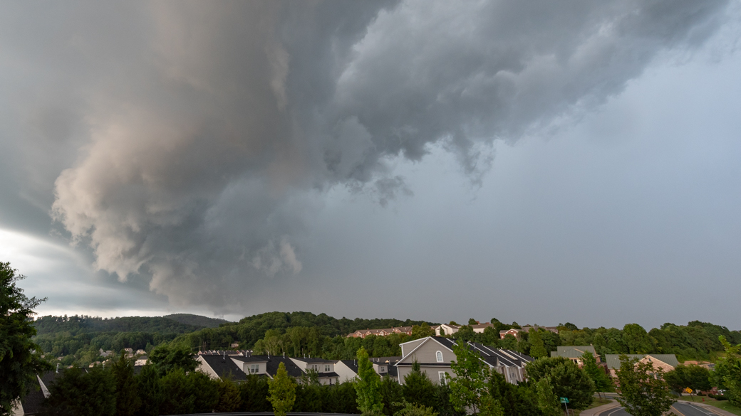 A photograph of a cumulonimbus arcus praecipitatio cloud (Cb arc pra) over a neighborhood