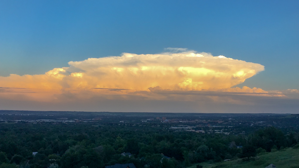 A photograph of a cumulonimbus capillatus incus velum cloud (Cb cap inc vel) at sunset over eastern Colorado